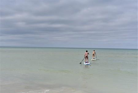 Two girls wearing bikinis are enjoying paddleboarding Banque d'images - 120853375