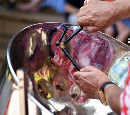 Musicians hands are skillfully performing calypso music with a Jamaican steel drum