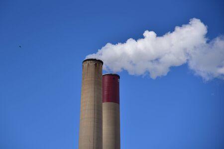 Smoke stacks spewing white fluffy water vapor