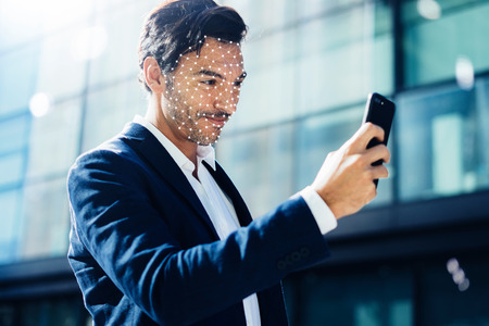 Man unloking his smartphone with Face ID system Stock Photo