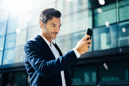Man unloking his smartphone with Face ID system Foto de archivo