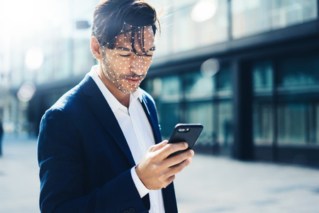 Man unloking his smartphone with Face ID system 스톡 콘텐츠
