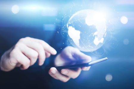 Man using smartphone with abstract globe at workplace