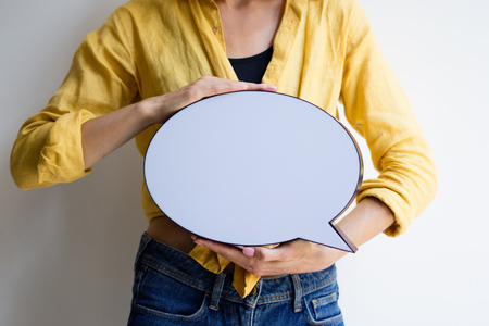 Young woman holding speech bubble