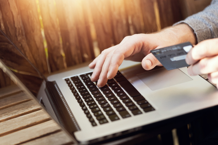 Close up of hands with bank card and laptop