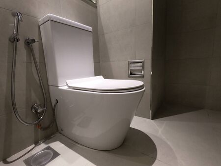 New ceramic toilet bowl, faucet and paper holder. Toilet bowl in modern bathroom interior with grey walls and grey floor.