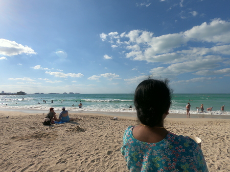 Dubai UAE - April 2019: Woman looking at the beach and the waters. View of blue water and partially cloudy sky. Unidentified people on the beach.