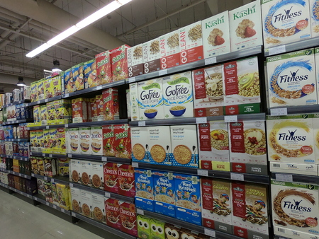 Dubai UAE - May 2019: A variety of packaged breakfast cereals on shelves for sale. Lanes of shelves with goods products inside. Cereal department and breakfast. Granola packed in the paper box, plasti