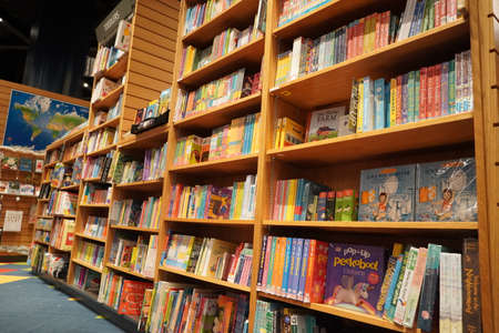 Children drawing and coloring books on shelves in a bookstore for sale. Library kids books section. Variety of Books For Sale On Bookshelf In Library. Supermarket. Dubai UAE December 2019.