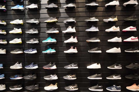 Shop display of a lot of Sports shoes on a wall. A view of a wall of shoes inside the store. Modern new stylish sneakers running shoes for men and women - Dubai UAE December 2019