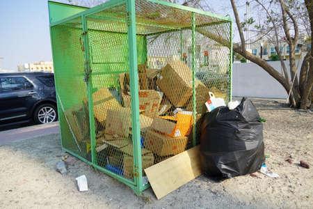 Dubai EMIRATI ARABI UNITI Dicembre 2019 Traboccante sacco della spazzatura nero pieno isolato. Sacchi della spazzatura, sacchi della spazzatura neri. Ambiente e concetto di oggetto. Lotto di scatole di cartone vuote sul retro. Zona residenziale.