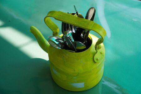 Kitchen utensils and cutlery in old fashioned green vintage teapot in bucket on table along with pepper shaker. Vintage Whistling kettle on green table. Stockfoto