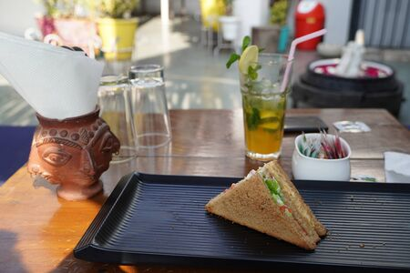 A single Tuna sandwich on black serving plate. One Club Sandwich with chicken, ham, cheese, tomatoes, cucumber, bacon, lettuce, herbs and toasted bread. Front view with blurred background.