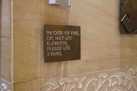 A sign that says, In Case Of Fire, Do Not Use Elevator, Please Use Stairs, which direct people of what to do in case of an fire emergency.