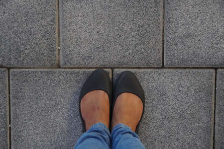 Women Black casual shoes standing and resting on asphalt concrete floor with square tiles. Top View. Concrete floor texture pattern pavement background. Selfie Female of Feet and Legs Seen from Above.