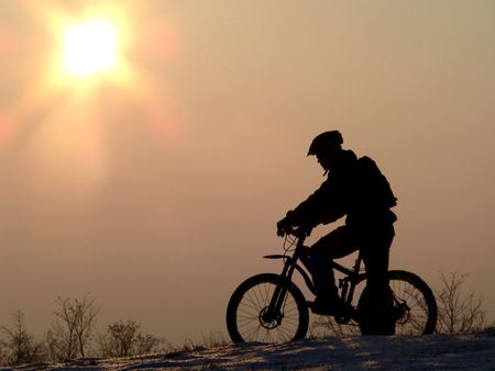 mountain biker silhouette in winter sunset photo