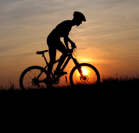 mountain biker silhouette in sunrise Stock Photo
