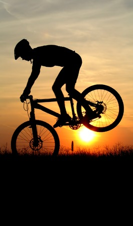 mountain biker silhouette in sunrise Stock Photo