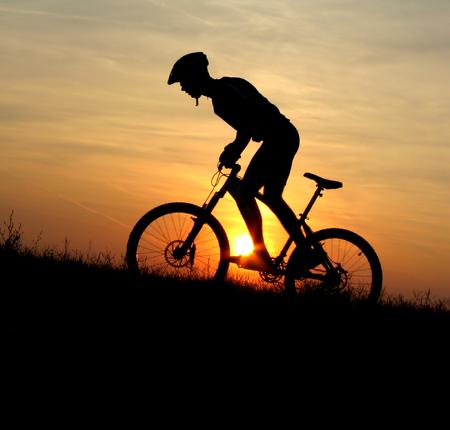 course cycliste: Mountain biker silhouette dans Sunrise