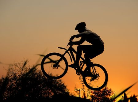jump with a mountain bike and orange sunset Stock Photo