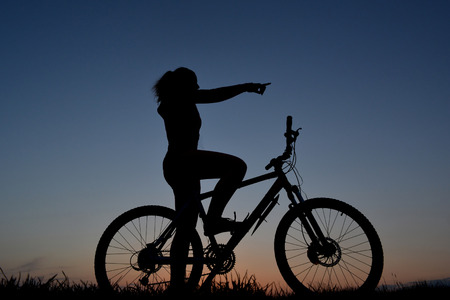 Mountain biker girl silhouette in sunset photo