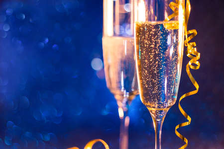 Christmas and New Year holiday background with two goblet,wine glass champagne and blue bokeh effect background.Selective focus . 写真素材