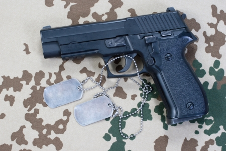 camouflaged: sig sauer hand gun and dog tags on desert camouflaged background
