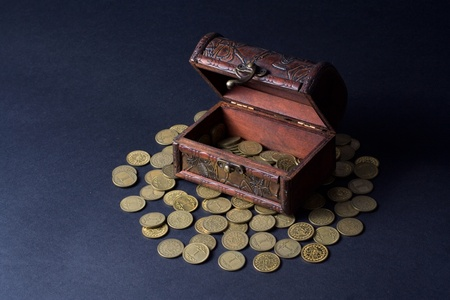 Old wooden chest with coins over gray background photo