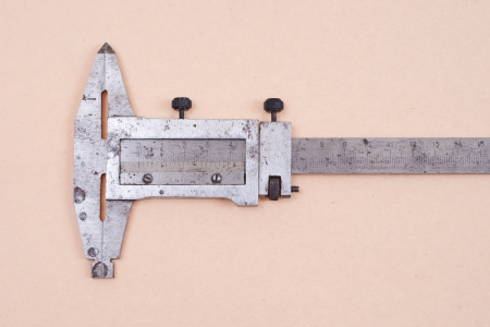 Vernier calipers isolated on old paper background photo