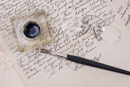 calligraphy pen:  retro ink pen on old aged paper isolated on white Editorial