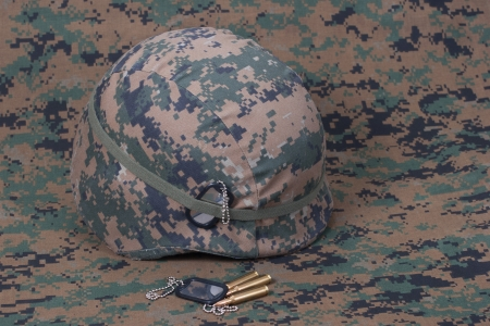 kevlar: kevlar helmet with dog tags and cartridges on camouflage cover