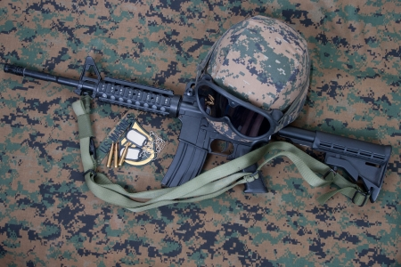 M4 carbine, kevlar helm with goggles and blank dog tags on us marines camouflage uniform