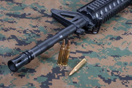 m4 carbine on camouflage uniform photo