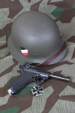 sidearm: Parabellum handgun, helm and medal Iron Cross on camouflaged background
