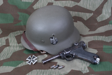 luger: Luger P08 Parabellum handgun, helm and medal Iron Cross on camouflaged background