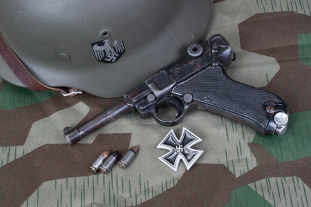 sidearm: Luger P08 Parabellum handgun, helm and medal Iron Cross on camouflaged background