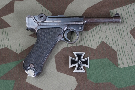 luger: Luger Parabellum handgun and medal Iron Cross on camouflaged background Editorial