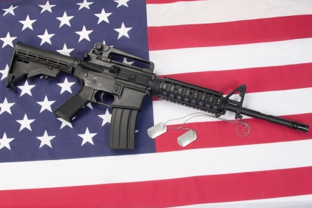 M4A1 carbine with blank dog tags on us flag photo
