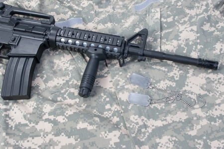 M4 carbine with blank dog tags on camouflage uniform photo