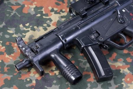 camouflaged: german modern submachine gun MP5 on camouflaged background