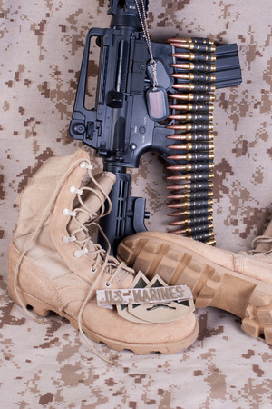 US Marines concept with firearms, boots and camouflaged uniform photo