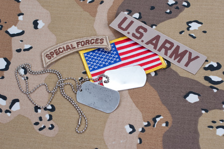 US ARMY special forces tab with blank dog tags on camouflage uniform photo