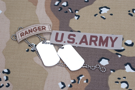 US ARMY ranger tab with blank dog tags on camouflage uniform photo