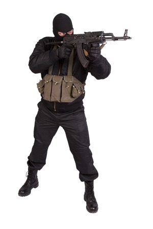 hijacker: terrorista en uniforme negro y la m�scara con kalashnikov aislado Foto de archivo