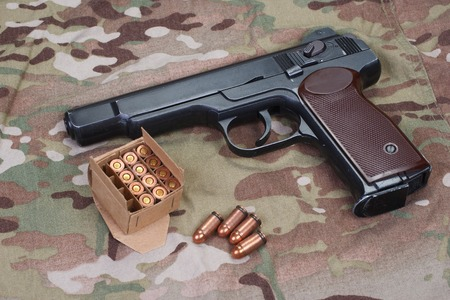 9mm ammo:  Stechkin automatic pistol APS on camouflage background