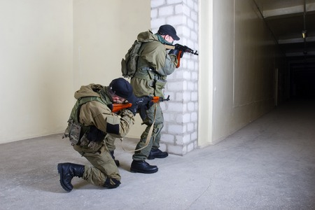 insurgents with AK 47 inside the building Stock Photo