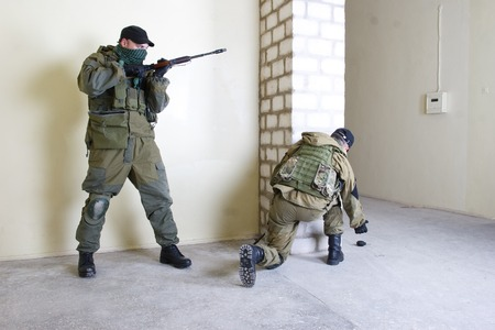 insurgents: insurgents with AK 47 throws a grenade inside the building