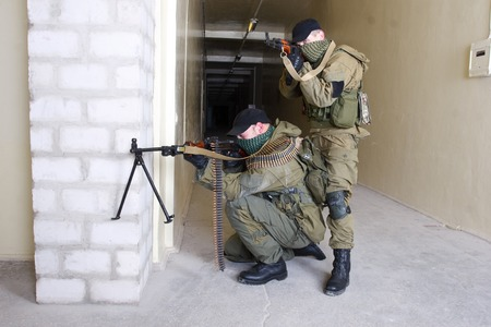 machinegun: insurgents with AK 47 and gun inside the building