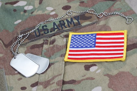 camouflaged: us army camouflaged uniform with US flag patch and blank dog tags