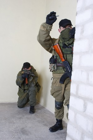 ak 47: insurgents with AK 47 throws a grenade inside the building